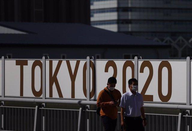 Japonenses utilizan mascarillas durante la pandemia de COVID-19 con un cartel de los Juegos Olímpicos de Tokio a sus espaldas