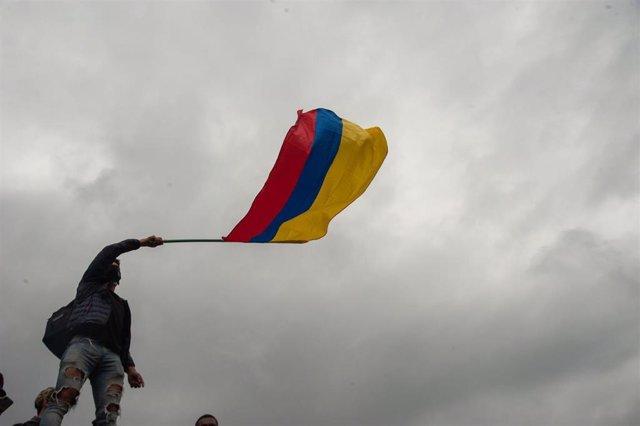 Archivo - Un joven ondea la bandera de Colombia