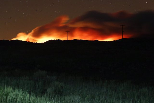 09 July 2021, US, Beckwourth: Flames and smoke rising from the Beckwourth complex wildfire illuminate the sky as it approaches highway 395 in the night. Photo: Ty Oneil/SOPA Images via ZUMA Wire/dpa