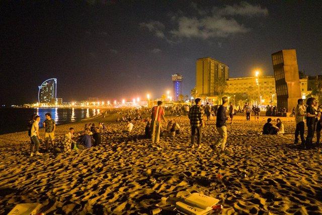 Joves es reuneixen en la platja de la Barceloneta hores abans que entri en vigor el toc de queda a Catalunya