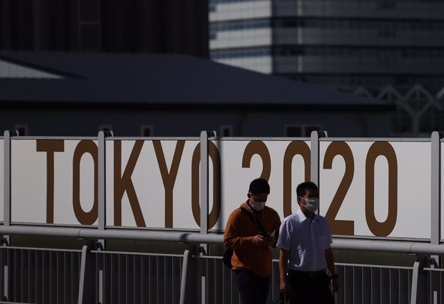Japonenses utilitzen mascarillas durant la pandèmia de COVID-19 amb un cartell dels Jocs Olímpics de Tòquio a les seves esquenes