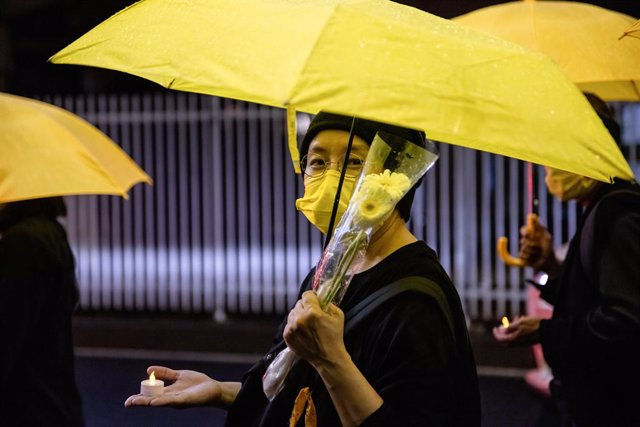 01 July 2021, Japan, Tokyo: A protester holding flowers and an umbrella, during a demonstration to mark the 100th anniversary of the founding of the CCP (Chinese Communist Party) and the 24th anniversary of Hong Kong's handover to China. Photo: Viola Kam/