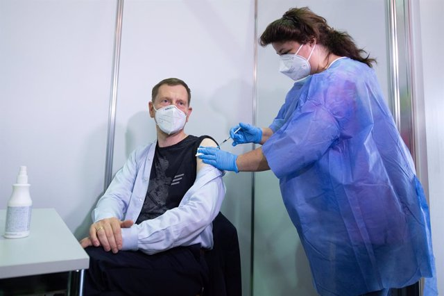 09 July 2021, Saxony, Dresden: Nurse Steffi Gehrmann (R) inoculates Michael Kretschmer, Prime Minister of Saxony, with AstraZeneca vaccine at the Vaccination Centre Saxony. During his visit to the vaccination centre, Kretschmer thanked the helpers for the