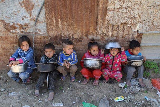 Niños palestinos esperan para recibir comidas benéficas en el barrio de Al Zaitún, en el este de la ciudad de Gaza