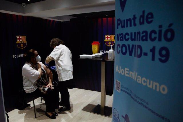Archivo - Arxivo - Una dona rep la primera dosi de la vacuna de Pfizer contra el Covid-19 en el Camp Nou de Barcelona.