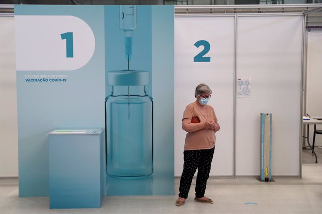 16 July 2021, Portugal, Lisbon: A woman waits outside a vaccination booth to be vaccinated against the corona virus at the Alcabideche sports complex. Portugal is accelerating its Corona vaccination campaign due to the rapid spread of the Delta variant in