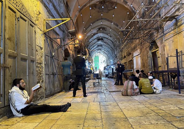 18 July 2021, Israel, Jerusalem: A group of ultra-Orthodox Jewish people pray in the Old City of Jerusalem near the entrance to the al-Aqsa mosque compound. Israeli security forces stand guard at a closure during the annual Tisha B'Av fasting and memorial