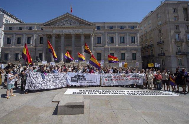 Varias decenas de personas participan este domingo, 18 de julio, en una concentración contra la impunidad del Franquismo, frente al Congreso de los Diputados