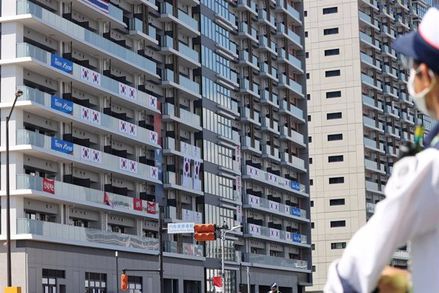 """17 July 2021, Japan, Tokyo: An official removes banners with the words """"I still have support from 50 million Korean people"""" from balconies at the athletes' village of the 2020 Tokyo Olympic Games. Photo: -/YNA/dpa"""