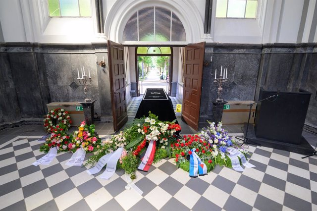 18 July 2021, Hamburg: The coffin of concentration camp survivor Esther Bejarano, stands surrounded by wreaths of flowers in front of mourners during her funeral service in Hamburg Chapel. Esther Bejarano, a Jewish woman who survived Auschwitz concentrati