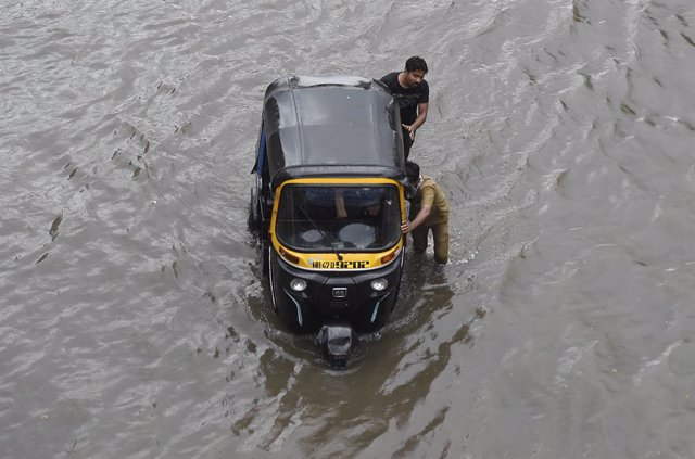 Archivo - 12 June 2021, India, Mumbai: People push an auto rickshaw as they wade through a waterlogged street as heavy rain continues, at Sion in Mumbai. Photo: Kunal Patil/PTI/dpa