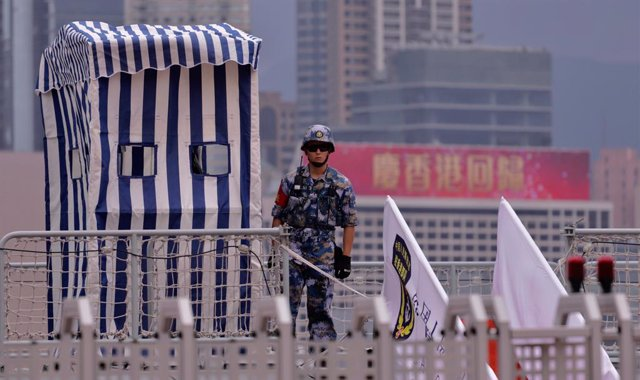 01 July 2021, China, Hong Kong: A Chinese People's Liberation Army Navy soldier stand guard on the deck of a battle ship being anchored at Admiralty Central. Today marks 24th anniversary of Hong Kong's Handover and 100th anniversary of the Chinese Communi