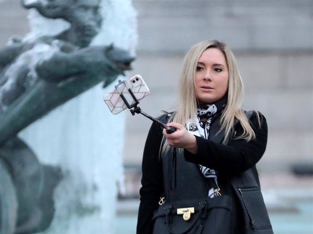 Archivo - A woman takes a selfie photograph on a smartphone in front of the frozen fountains of Trafalgar Square on February 11, 2021 in London, England.