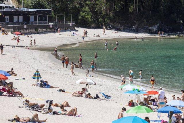 Archivo - Varias personas se bañan y toman el sol en una playa del municipio de Marín, en Pontevedra