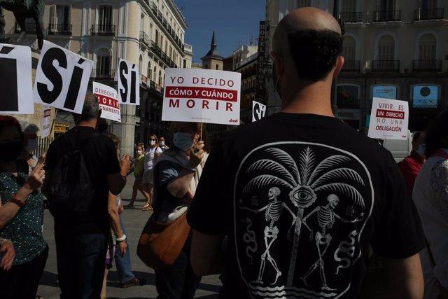 Un grupo de personas se reúne sosteniendo pancartas y carteles durante la concentración de la asociación Derecho a Morir Dignamente (DMD) en la Puerta del Sol, a 25 de junio de 2021, en Madrid, (España).