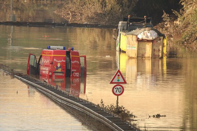 18 July 2021, North Rhine-Westphalia, Erftstadt: A fire brigade emergency vehicle and a truck are still stuck in water on the B265 near Erftstadt Liblar after deadly floods that hit North Rhine-Westphalia. Photo: David Young/dpa