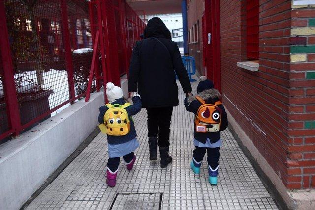 Archivo - Un adulto lleva de la mano a dos alumnos a un colegio de Madrid.