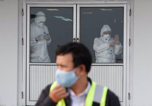Archivo - Trabajadores con trajes protectores en Tailandia.