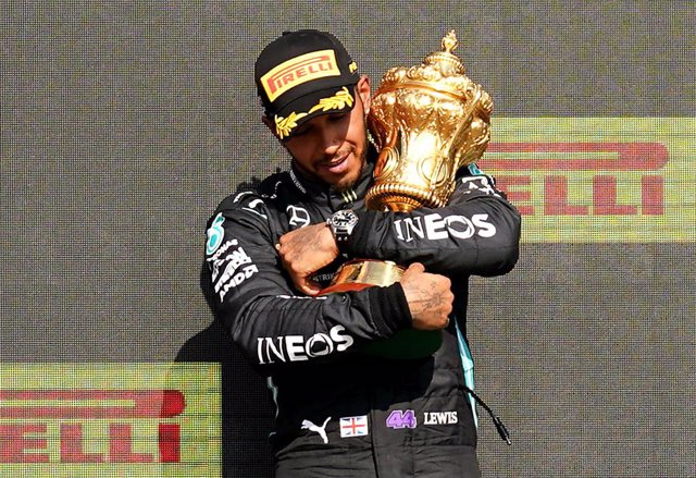 18 July 2021, United Kingdom, Towcester: British F1 driver Lewis Hamilton of Mercedes AMG Petronas, celebrates on the podium with the trophy after winning the Formula One Grand Prix of Britain at the Silverstone Circuit. Photo: Tim Goode/PA Wire/dpa