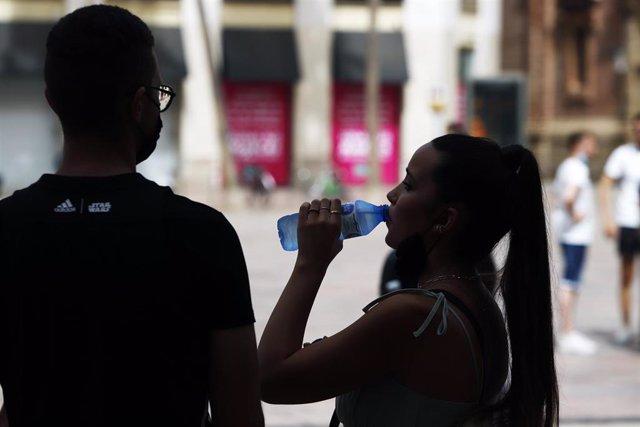 Varias personas intentan protegerse del calor en el día donde la capital andaluza se encuentra  en  aviso naranja por temperaturas que superarán los 40 grados en algunos puntos de la capital y la provincia a 12 de julio del 2021 en Málaga (Andalucía). Se