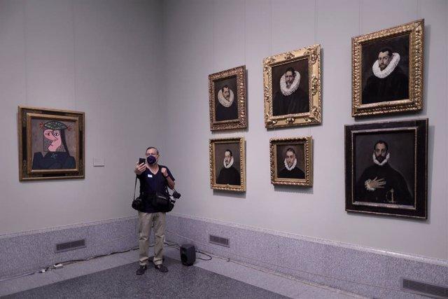 Un hombre se hace una fotografía junto a los retratos de 'El Greco' de Doménikos Theotokópoulos y junto a la obra 'Busto de mujer 43', de Pablo Picasso, el día de la presentación de la instalación en el Museo del Prado.