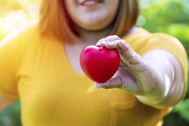 Archivo - Mujer con obesidad sujeta en su mano un corazón. Salud cardiovascular.
