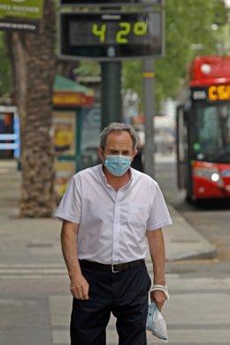 Un anciano pasea con mascarilla junto a un termómetro que marca 42º durante un día de alerta roja por altas temperaturas, a 12 de julio de 2021, en la ciudad de Murcia, Murcia (España). Las provincias de Alicante, Valencia y Murcia tienen este lunes aviso