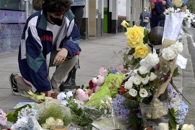Un joven se arrodilla ante el altar colocado en la acera donde fue golpeado Samuel.