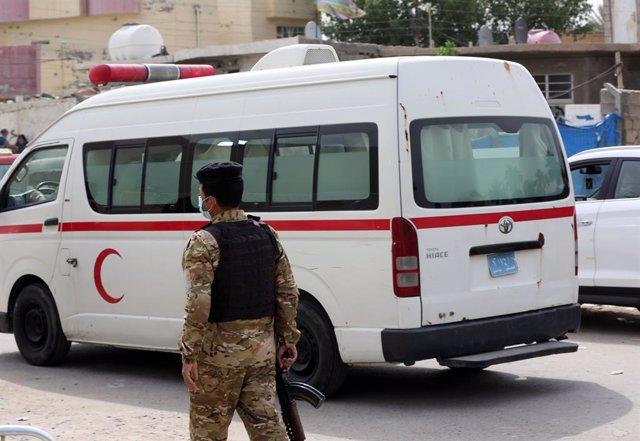 Un policía junto a una ambulancia en Bagdad