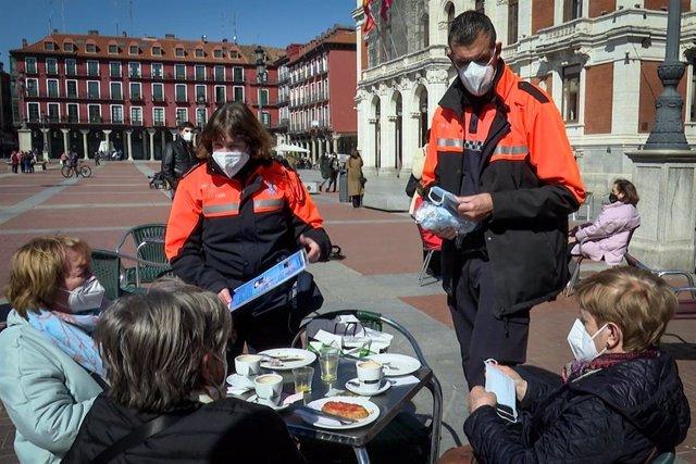 Archivo - Voluntarios de Protección Civil informan sobre las medidas sanitarias a tres clientas de una terraza de Valladolid que cumplen correctamente la normativa.
