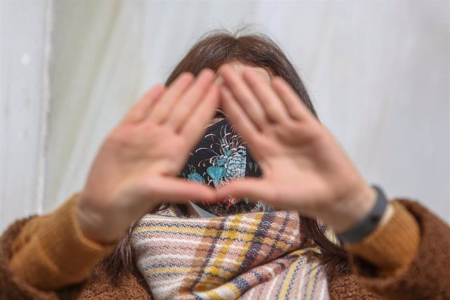 Archivo - Una mujer hace uno de los símbolos feministas con las manos durante una concentración en Madrid.