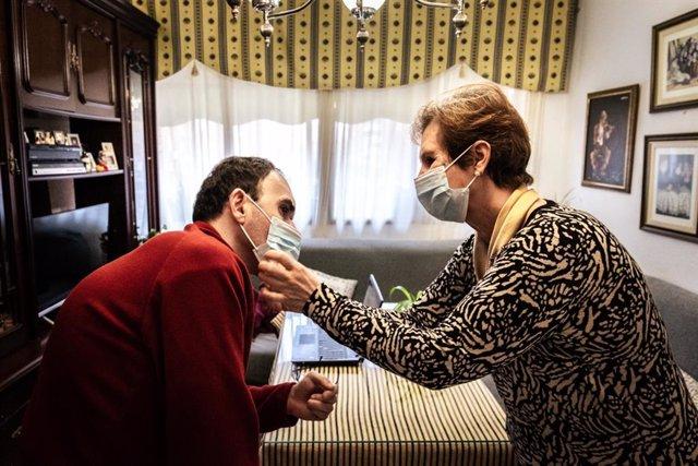 Archivo - Una mujer ayuda a su hijo con discapacidad a colocarse la mascarilla.