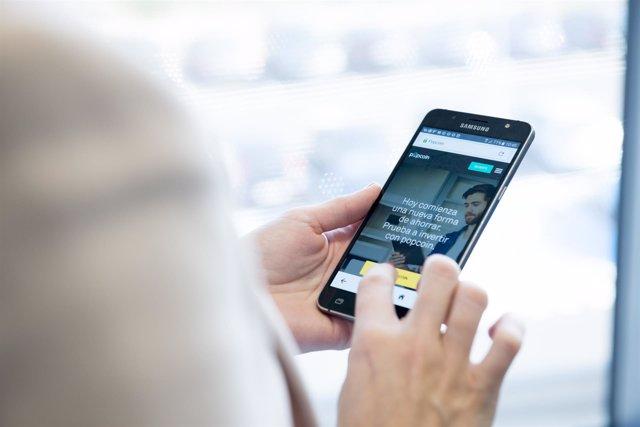 Archivo - Una persona maneja en su móvil la aplicación de Popcoin, el roboadvisor de Bankinter