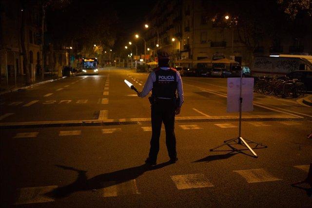 Archivo - Un mosso d'Esquadra colabora en un control durante el toque de queda impuesto por la crisis sanitaria del Covid-19 desde las 22.00 horas a las 6.00 del día siguiente, en Barcelona, Catalunya, (España), a 6 de noviembre de 2020. Según indican los