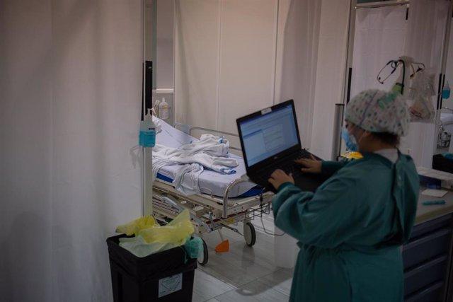 Archivo - Una sanitaria toma datos en su ordenador en una de las habitaciones de la Unidad de Cuidados Intensivos