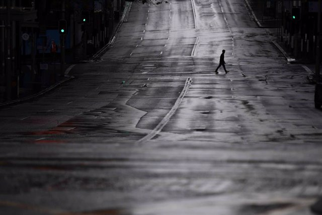 FILED - 29 June 2021, Australia, Sydney: A pedestrian crosses an empty Bridge Street in Sydney. More than five million people in Greater Sydney and its surrounds have gone into a 14-day lockdown as health authorities try to regain control of a coronavirus