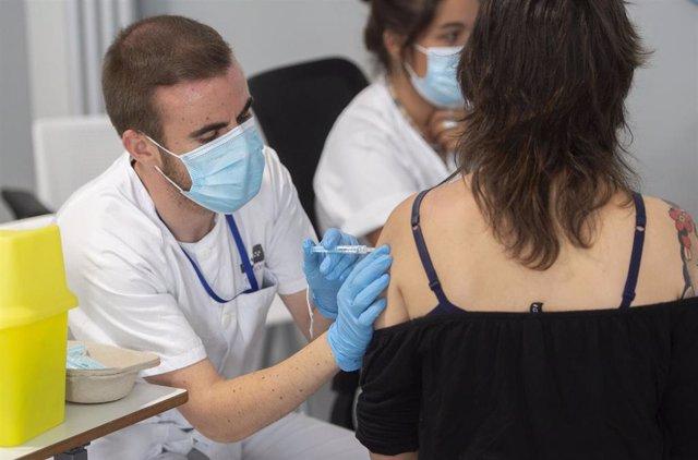 Una joven recibe la primera dosis de la vacuna Pfizer en el Hospital Zendal