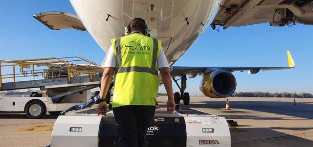 Imagen de un operario de WFS dirigiendo el nuevo 'pushback' mientras remolca una aeronave