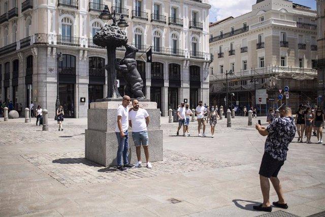 Un hombre toma una foto a otros dos, sin mascarilla en la Puerta del Sol,