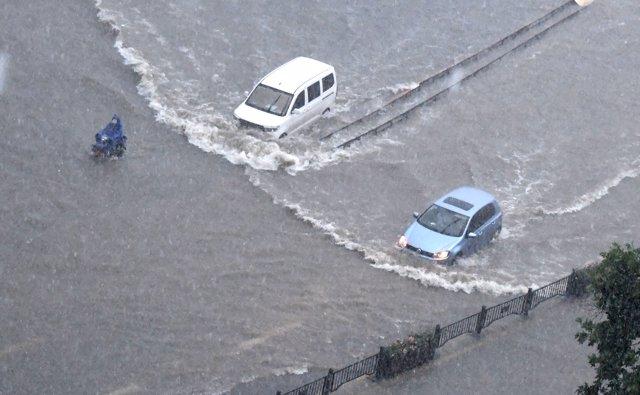 Vehículos circulan por una carretera anegada en Zhengzhou, capital de la provincia de Henan.