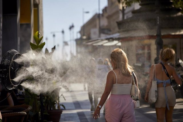 Varias personas caminan al lado de un difusor de vapor de agua, en una foto de archivo