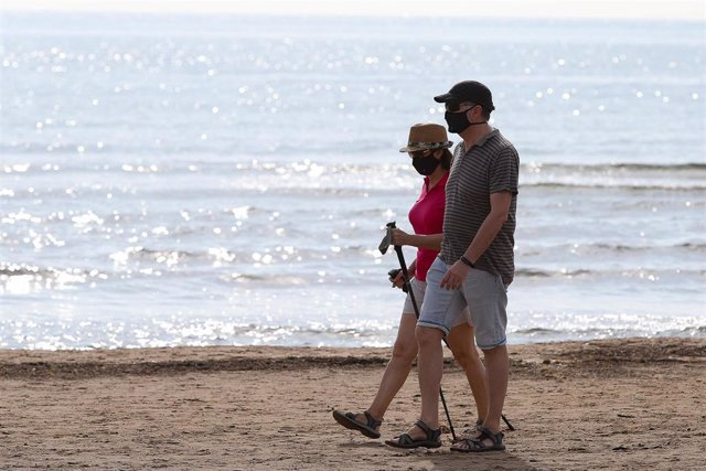 Archivo - Dos personas protegidas con mascarilla pasean por la playa de la Malvarrosa.