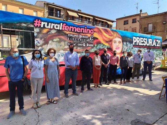 La consejera Esnaola, autoridades locales, participantes en la mesa redonda y responsables de la iniciativa posan junto al autobús en Los Arcos