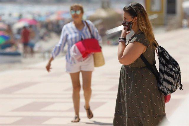 Una mujer con mascarilla pasea por el paseo marítimo de la playa de La Manga.