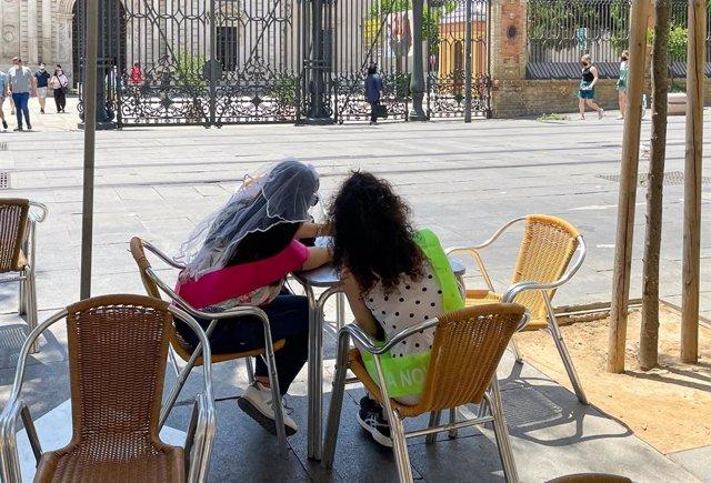 Archivo - Dos jóvenes, ataviadas con la vestimenta de las despedidas de soltera, en la terraza de un bar de la calle San Fernando de Sevilla en pleno escenario pandémico, foto de recurso