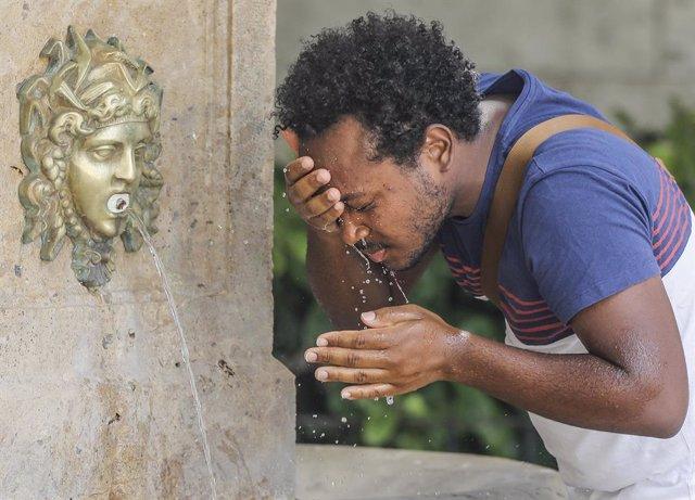 Un hombre se refresca en una fuente del centro de Valencia para soportar las altas temperaturas, a 12 de julio de 2021, en Valencia, Comunidad Valenciana (España). Las provincias de Alicante, Valencia y Murcia tienen este lunes avisos de nivel rojo (riesg