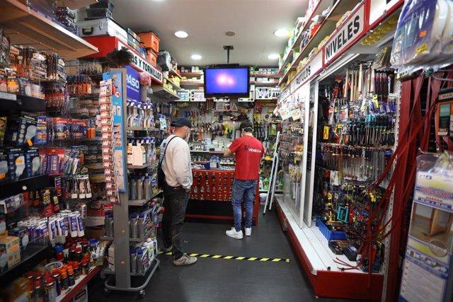 Archivo - Un dependiente atiende a un cliente en la Ferretería Venecia (calle Bravo Murillo, 12)