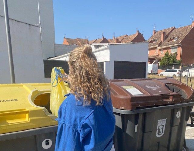 Una mujer deposita envases domésticos en el contenedor amarillo.