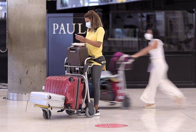 Una mujer con equipaje, durante el día en el que se pone en marcha el certificado COVID Digital para garantizar la movilidad segura ante la COVID19, en la T4 del aeropuerto Adolfo Suárez, Madrid-Barajas.