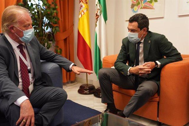 El presidente de la Junta de Andalucía, Juanma Moreno (d), se reúne con representantes de la Confederación Nacional de Asociaciones de Comerciantes de Cascos Históricos de España.